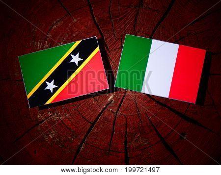 Saint Kitts And Nevis Flag With Italian Flag On A Tree Stump Isolated