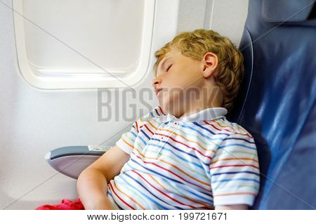 Little kid boy sleeping during long flight on airplane.