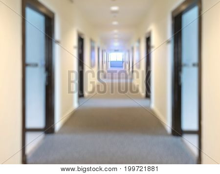 Blurred Corridor with lots of dark brown doors. White walls and ceiling concrete floor. Concept of hotel lobby.