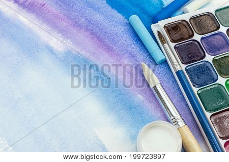 Paints Palette With Paintbrushes And Pastel Crayons On Blue Watercolor Background
