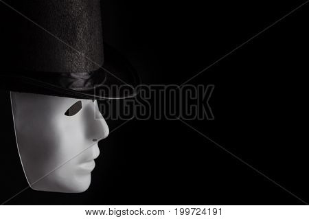 White mask profile wearing black top hat isolated on black background with copy space