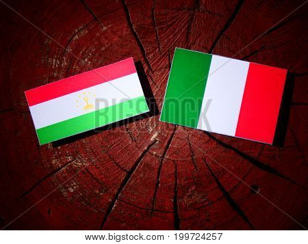 Tajikistan Flag With Italian Flag On A Tree Stump Isolated