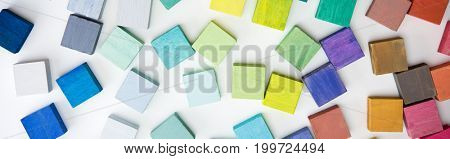 Multi colored wooden blocks on white table.  Background or cover for something creative or diverse.