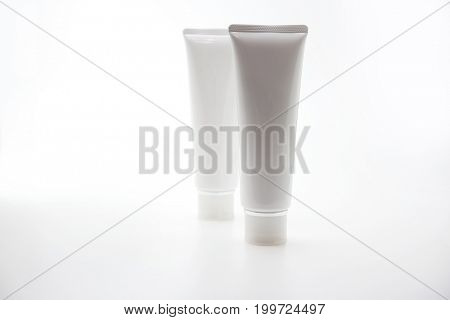 Two blank cosmetic type white glossy tube isolated on natural white background.