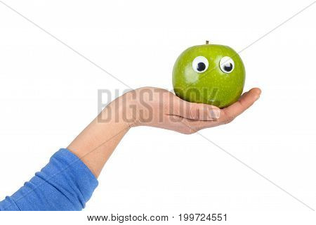 Female hand holding green apple with googly eyes isolated on white background with copy space. Healthy food and lifestyle concept