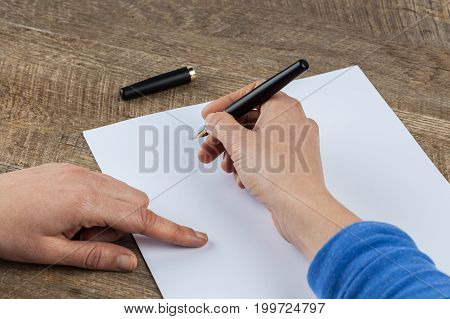 Woman hands holding fountain pen and blank piece of paper on wooden table