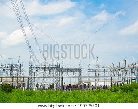 high voltage power plant and transformation station at sunset : selective focus at barbed wire