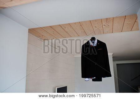 Groom's Wedding Suit Hanging On The Rack In Big Light Room.