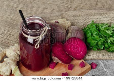 Close-up of a mason jar of beetroot juice with black straw on a wooden background. Whole and cut beetroots, ginger and parsley on a fabric. A lot of healthy ingredients for cooking on a cutting board.