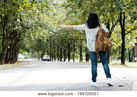 Blurred woman with backpack hitchhiking on the countryside road background travel concept