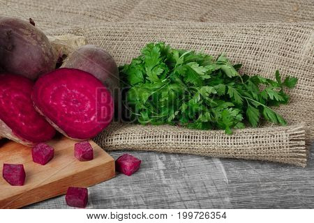 Close-up of a composition of whole and sliced beetroots and green parsley on a light fabric and on a wooden background. Fresh herbs and beets for salads or smoothies on a cutting board.