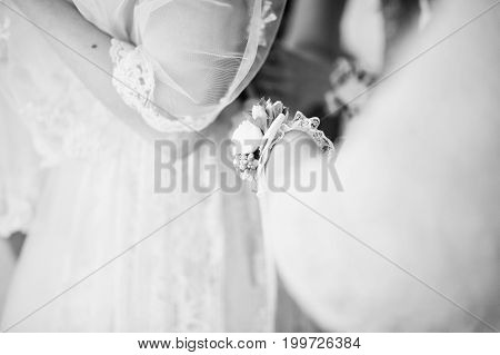 Helpful Bridesmaids And Mother Helping Bride To Tie The Dress Up In Big Light Room. Black And White