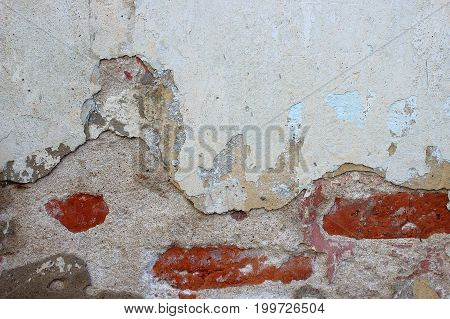 Grey grungy wall.Old brick wall. The crumbling wall of bricks. Wall texture background. The plaster on the wall. Uneven wall surface. The paint on the wall. Plastered walls. Abstract background. Painted brick wall