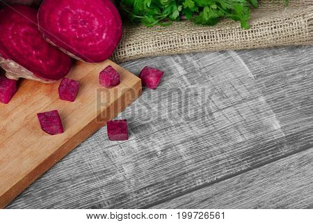 A view from above of a composition of whole and sliced beetroots and green parsley on a light fabric and on a wooden background. Fresh herbs and beets for salads or smoothies on a cutting board.