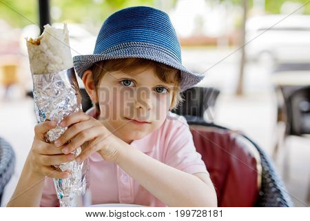 Cute healthy preschool kid boy eats turkish kebab wrap sitting in cafe outdoors. Happy child eating unhealthy food in restaurant.