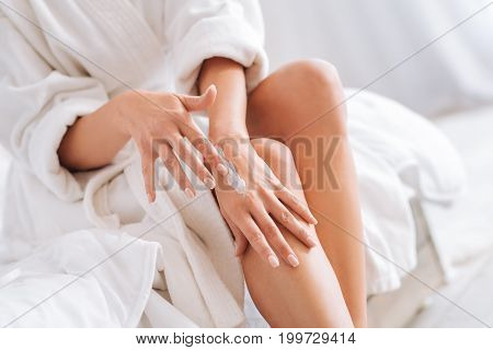 Take care. Happy young woman sitting on her bed and relaxing after shower while testing new cream