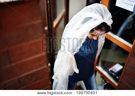 Portrait Of A Beautiful Bride Wearing Casual Clothes And Veil Walks Out Of The Room.