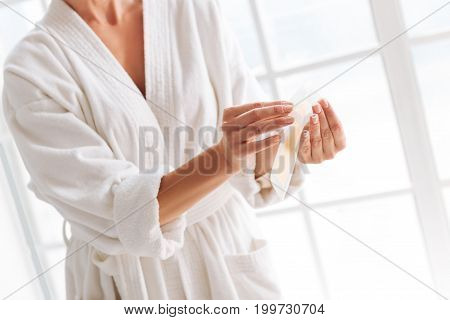 Ready to use it. Young woman standing in her room near window while warming up beeswax stripes for doing epilation