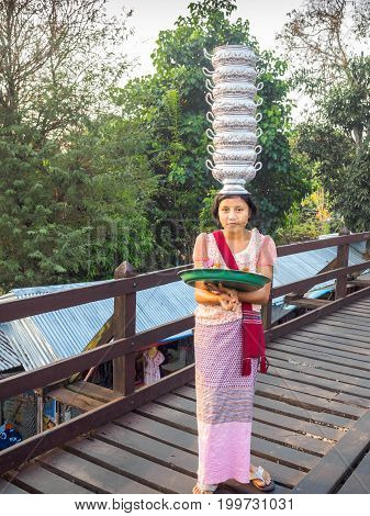 Sangkhlaburi Thailand- March 05 2017: The unidentified Mon woman selling is selling flowers for tourists at the Mon bridge while showing her skill in holding empty cooked-rice bowls on her head.