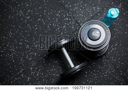 Top view of a blue bottle for water and two heavy metal dumbbells, equipment used in pairs, in workouts by wrestlers, bodybuilders, sports players, routines, gyms on a dark blurred background.