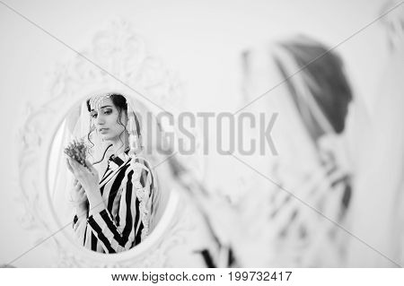Portrait Of A Fantastic Bride Posing With Lavender Flowers In The Mirror. Black And White Photo.