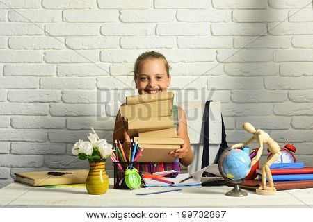 Girl Near Flowers, Globe And Colorful Stationery On Her Desk