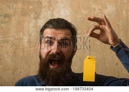 Man with beard on happy face. Guy hold shopping tag. Sale and shopping. Black Friday in shop. Businessman take paper.