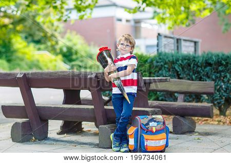 Happy little kid boy with glasses and backpack or satchel on his first day to school .