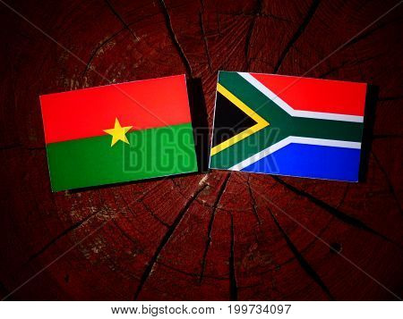Burkina Faso Flag With South African Flag On A Tree Stump Isolated