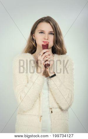 fun woman eating sausage on white background