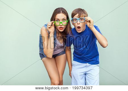 Eyewear concept. WOW faces. Young sister and brother with freckles on their faces wearing trendy glasses posing over light green background together. Looking at camera with surprised face. Studio shot
