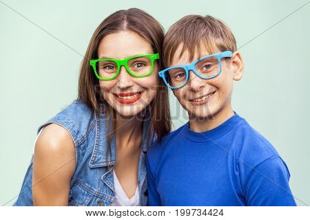 Eyewear concept. Hipster style. Portrait of gorgeous freckled brother and sister in casual t shirts wearing trendy glasses and posing over light blue background together. Studio shot