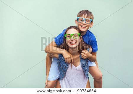 Hipster style. Eyewear concept. The gorgeous freckled brother and sister in casual t shirts wearing trendy glasses and posing over light blue background together. Brother climbed up on the back of a cute sister. Studio shot