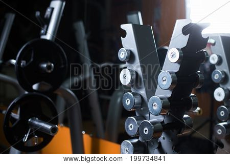 A stand with heavyweight black barbells and chrome dumbbells holder on a dark blurred gym background. Professional gym equipment for bodybuilders. Powerful workout and physical training concept.