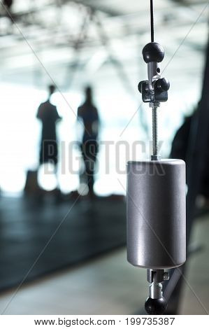 Close-up of a single shiny standard calibration weight on a blurred light gym background. Steel scales dumbbell for measurement, exercising, physical trainings and weightlifting. Copy space.