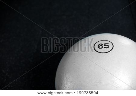 A close-up picture of a huge, white gymnastics ball on the black floor background. A view from above on a fit ball for aerobics, pilates and fitness trainings. Minimalistic gym ball for workout.