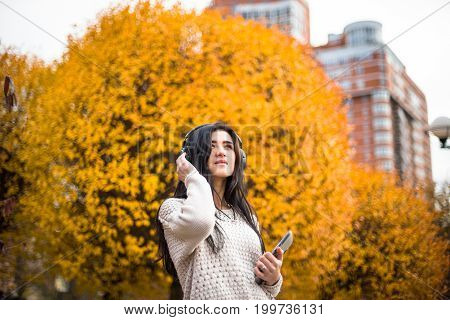 Happy teen woman relax in autumn park. Yellow trees, beautiful fall time.