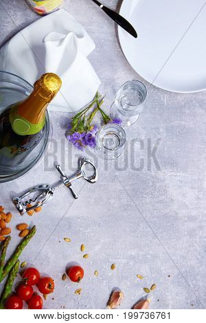 Close up of a white plate, red bright tomatoes, twigs of asparagus, almond, a bottle of champagne, silver corkscrew, snow-white napkin, knife and fork on a grey background.
