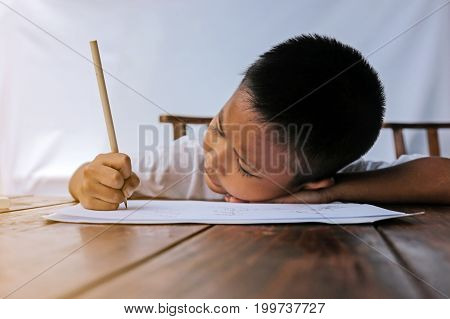 Asian little boy drawing intently on wooden table with orange sunlight and white background. Little painter concept.