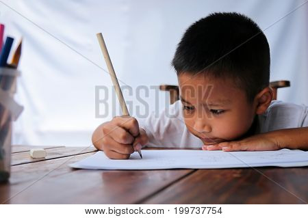 Asian little boy drawing intently on wooden table with sunlight and white background. Little painter concept.