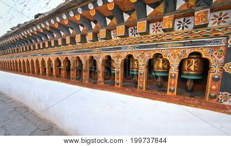 Rows of colorful religious prayer wheels in Paro Rinpung Dzong. Buddhist monastery and fortress at Paro Bhutan.