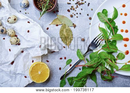 A white plate with drops of sauce and fresh green leaves, bay leaves, a half of juicy yellow lemon, little speckled quail eggs, a jar with different seasonings on a light gray background, top view.