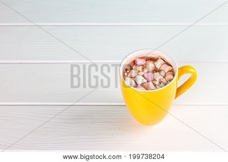 Yellow cup of hot cocoa with marshmallows on white wooden background