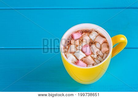 Yellow cup of hot cocoa with marshmallows on blue wooden background