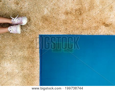 View of girl legs and pink shoes at swimming pool side background textured.
