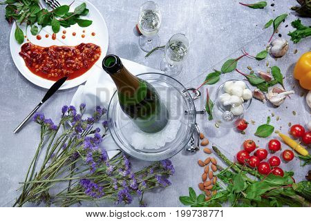 Close-up of a table with a white plate with canned beans with red sauce, a green bottle of champagne, little violet flowers, cloves of garlic, salad pepper, salad leaves on a light gray background.