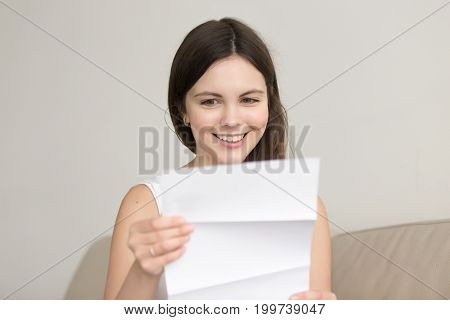 Surprised woman reading letter with unexpected good news, feeling excited about unbelievable offer in written notification, happy teenager enjoying successful positive result, passed exam, got hired