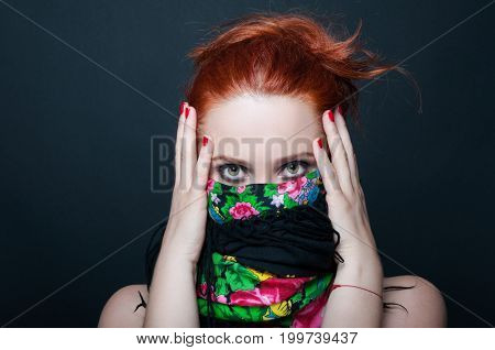 Young Redhead Girl With Floral Scarf Over Mouth
