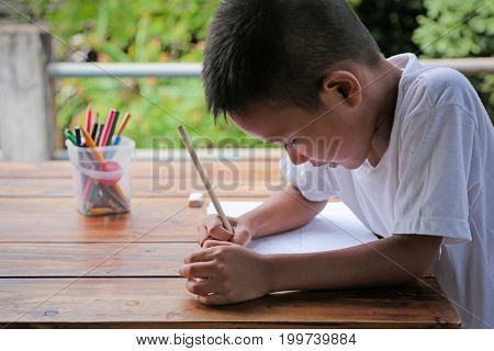 Asian little boy drawing intently on wooden table with nature blur background. Little painter concept.