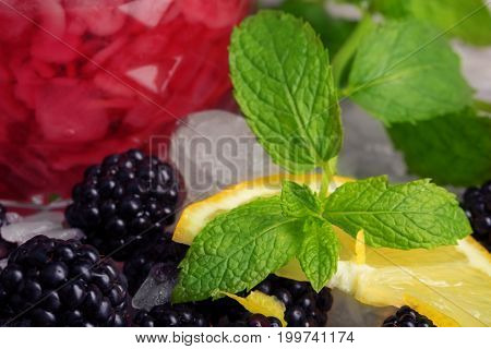 Close-up of aromatic fresh green leaves of mint, white pieces of ice, fragrant juicy blackberries, slices of yellow lemon and a glass of juice on a colorful blurred background. Summer berries.